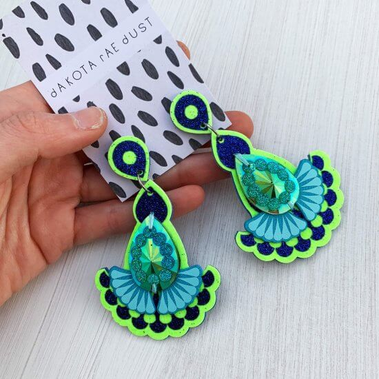A pair of neon green and glittery blue teardrop and fan shaped jewelled earrings adorned with an glittery green gem are seen mounted on a black and white patterned, dakota rae dust branded card, held by a white hand against an off white background