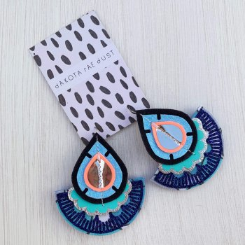 A pair a bright blue and turquoise oversize fan earrings on a black and white patterned dakota rae dust branded card, seen against a textured off white background