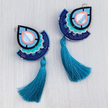 A pair of turquoise, blue, silver and coral large tasselled fan earrings lying side by side on an off white background. The silky turquoise tassels are curving in opposite directions.