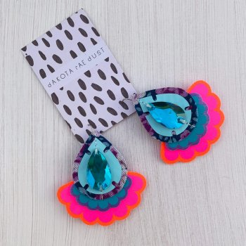 A colourful pair of teardrop shapes fluorescent pink, turquoise and blue oversize earrings featuring a bright scallop edged frill are seen displayed on a black and white dakota rae dust branded card, against a textured white background.
