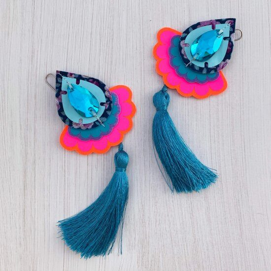 A pair of colourful teardrop shaped statement tassel earrings featuring turquoise jewels are seen lying on a textured white background. The earrings have turquoise tassels and fluorescent pink scallop edged trims.